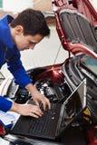Mécanicien à l'aide de l'ordinateur portable tout en réparant la voiture photographie stock libre de droits
