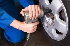 Mécanicien ajustant la roue de pneu photo libre de droits