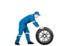 Mécanicien américain poussant une roue de voiture sur le studio Image stock