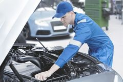 Mécanicien américain vérifiant la voiture dans l'atelier Photo libre de droits