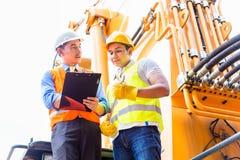 Mécanicien asiatique avec la machine de construction Images stock