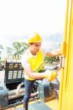 Mécanicien asiatique réparant le véhicule de construction Photo stock