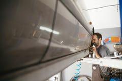 Mécanicien automatique réparant le véhicule Photographie stock