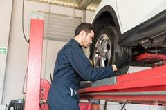 Mécanicien automobile Adjusting Car Tire dans l'atelier de réparations photographie stock