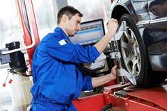 Mécanicien automobile au travail d'alignement des roues avec la clé photographie stock libre de droits