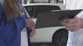 Mécanicien automobile de fille prenant des données au sujet de voiture et signées prenant la clé et serrant la main du jeune homm banque de vidéos
