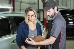 Mécanicien automobile et client féminin dans le garage image libre de droits