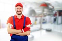Mécanicien automobile heureux se tenant dans le service de voiture image libre de droits