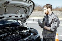 Mécanicien automobile réparant la voiture dehors image stock