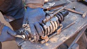 Mécanicien automobile travaillant à l'amortisseur dans le garage Photos stock