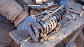 Mécanicien automobile travaillant à l'amortisseur dans le garage Image stock