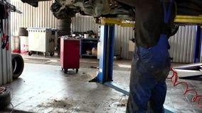 Mécanicien automobile travaillant à l'atelier de réparations automatiques Inclinaison vers le bas clips vidéos