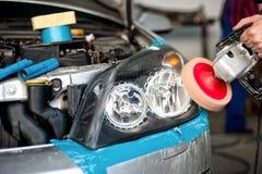 Mécanicien automobile travaillant à polir un phare de voiture Images stock