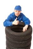 Mécanicien avec des pneus de véhicule au travail Photo stock