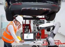 Mécanicien avec l'équilibrage robotique de roue d'inspection d'aide image stock