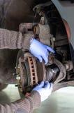 Mécanicien changeant les protections de frein d'une voiture photo libre de droits