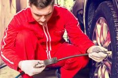 Mécanicien concentré de moteur vérifiant la pression atmosphérique d'un pneu Images libres de droits