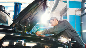 Mécanicien dans le service de voiture - réparant en compartiment réacteur pour SUV de luxe photo libre de droits