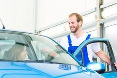 Mécanicien de client et de voiture dans l'atelier Image stock