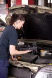 Mécanicien de femme avec l'outil de diagnostics d'engine Photo libre de droits