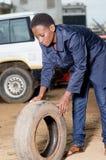 Mécanicien de jeune femme avec un pneu dans l'atelier de voiture Photographie stock libre de droits