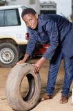 Mécanicien de jeune femme avec un pneu dans l'atelier de voiture Image stock