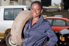 Mécanicien de jeune femme chargeant un pneu sur son épaule au garage Photos stock