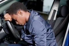Mécanicien de jeune femme s'asseyant à la roue d'une voiture Photographie stock