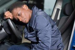 Mécanicien de jeune femme s'asseyant à la roue d'une voiture Images libres de droits
