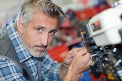 Mécanicien de plan rapproché travaillant au moteur d'essence Photos stock