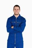 Mécanicien de sourire dans le procès de chaudière avec les bras pliés Image stock