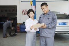 Mécanicien de sourire Explaining de garage au client, lui montrant le Bill Photo stock