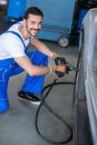 Mécanicien de sourire réparant la roue de voiture Photographie stock