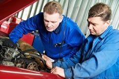 Mécanicien de véhicule deux diagnostiquant le problème automatique d'engine Image libre de droits