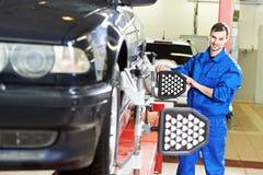 Mécanicien de voiture à l'alignement des roues avec l'ordinateur image stock