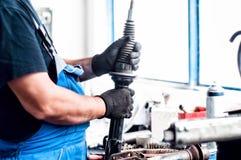 Mécanicien de voiture automatique ajustant un amortisseur de voiture Images libres de droits