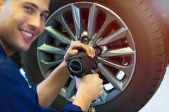 Mécanicien de voiture dans des pneus changeants d'atelier Image stock