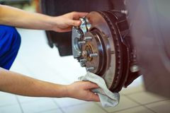 Mécanicien de voiture dans des pneus changeants d'atelier photographie stock libre de droits