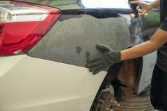 Mécanicien de voiture dans le service de voiture réparant des bosselures sur la carrosserie photographie stock libre de droits