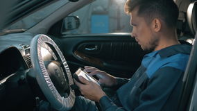 Mécanicien de voiture professionnel travaillant dans le service des réparations automatique moderne et vérifiant le moteur Images stock