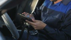 Mécanicien de voiture professionnel travaillant dans le service des réparations automatique moderne et vérifiant le moteur Image libre de droits