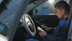 Mécanicien de voiture professionnel travaillant dans le service des réparations automatique moderne et vérifiant le moteur Photo libre de droits
