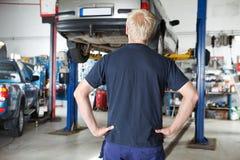 Mécanicien de vue arrière regardant le véhicule Image stock