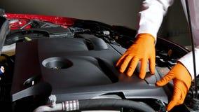 Mécanicien Disassembling la couverture de moteur d'une voiture banque de vidéos