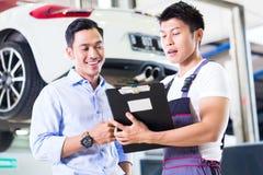 Mécanicien et client de voiture dans l'atelier automatique asiatique Photo stock