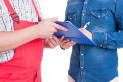 Mécanicien et client ou participation et écriture de client sur le presse-papiers Photographie stock libre de droits