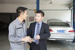Mécanicien Explaining de garage au client, lui montrant le Bill Photos stock