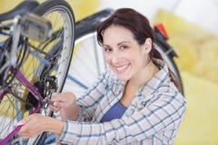 Mécanicien féminin dans l'atelier installant ou réparant la roue de bicyclette Photographie stock