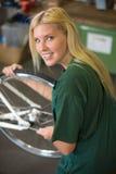 Mécanicien féminin dans l'atelier installant ou réparant une bicyclette photos stock