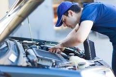 Mécanicien fixant un moteur de voiture photos stock